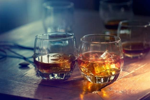 whiskey-bourbon-glass-with-ice-wooden-table-colorful-background_34200-15.jpg